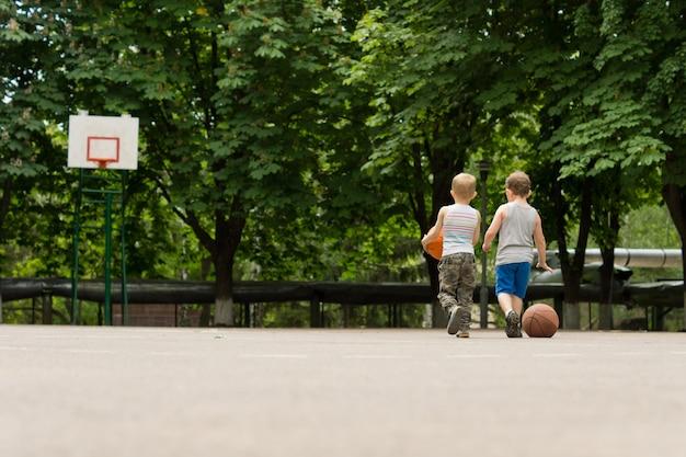 Widok z tyłu dwóch młodych chłopców idących po boisku do koszykówki