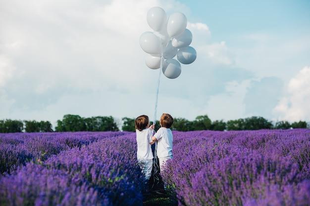 Widok z tyłu dwóch szczęśliwych chłopców trzymających się za ręce w lawendowym polu z białymi balonami