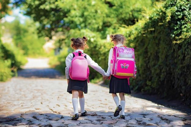 Widok z tyłu dwóch uczennic noszących plecak poza szkołą podstawową.