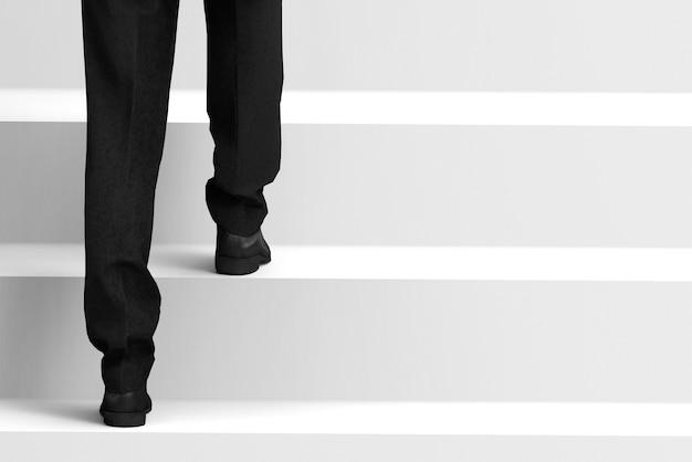 Widok z tyłu działalności człowieka, który wspina się na schody do celu sukcesu