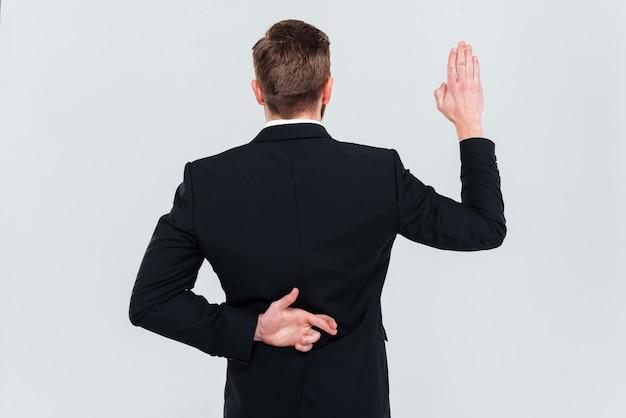 Widok z tyłu działalności człowieka w czarnym garniturze leżącego. trzymając się za rękę z palcami skrzyżowanymi za plecami i przeklinając. na białym tle szarym tle