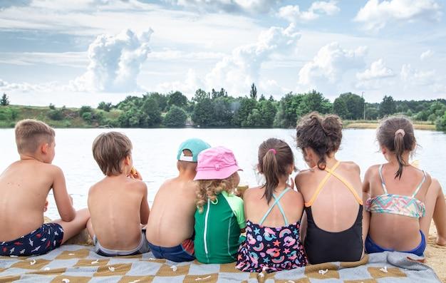 Widok z tyłu dzieci siedzą nad rzeką i odpoczywają po kąpieli, opalają się, jedzą lody.