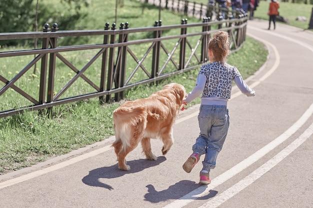 Widok z tyłu. dziewczyna i jej wierny pies na spacer