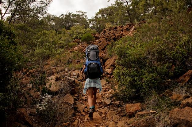 Widok z tyłu dziewczyna z plecakiem i laski piesze spacery po skałach