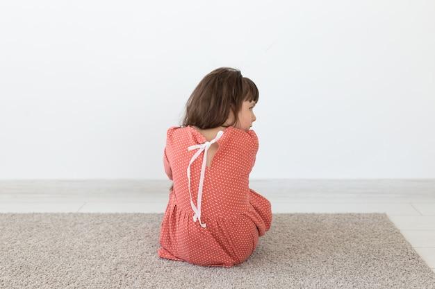 Widok z tyłu dziewczynki w czerwonej sukience w kropki siedzącej na podłodze na białej ścianie.