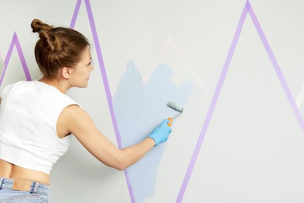 Widok Z Tyłu Dziewczyny Malującej ścianę Wałkiem Do Malowania I Używając Taśmy Maskującej, Stojąc Na Drabinie Premium Zdjęcia