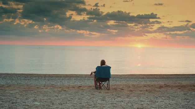Widok z tyłu dziewczyny podziwiającej zachód słońca nad morzem siedząc w składanym fotelu turystycznym