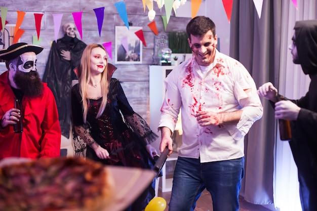Widok z tyłu dziewczyny przybywającej z pizzą na imprezie halloween.