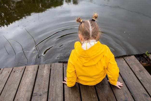 Widok z tyłu dziewczyny z śmiesznymi warkoczykami w żółtym płaszczu przeciwdeszczowym siedzi na drewnianym molo w deszczową pogodę