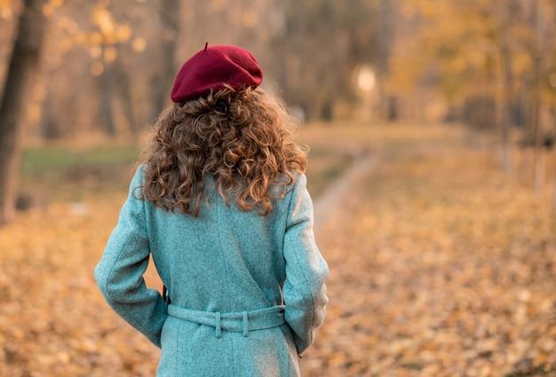 Widok z tyłu eleganckiej młodej kobiety w szarym płaszczu na co dzień jesienią.