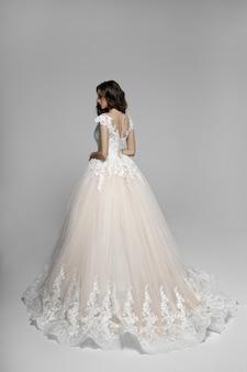 Widok z tyłu elegancko młoda kobieta w pięknej sukni wendding, na białym tle na białym tle.