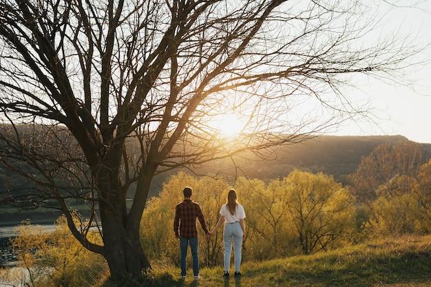 Widok z tyłu faceta i dziewczyny stoją razem i trzymają się za ręce pod wielkim starym drzewem pod ścianą lasu, wzgórza i rzeki o zachodzie słońca.