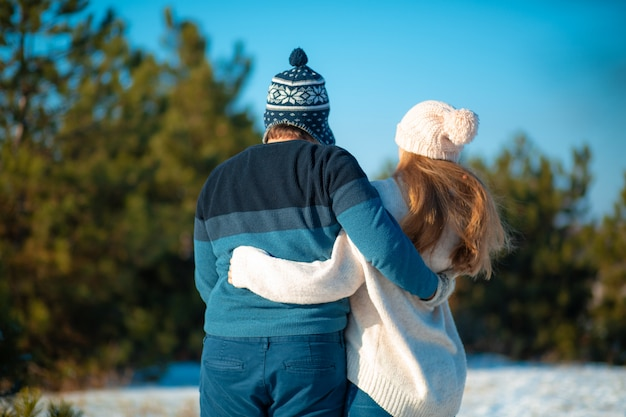 Widok z tyłu faceta z dziewczyną w objęciowym spacerze w zimowym lesie