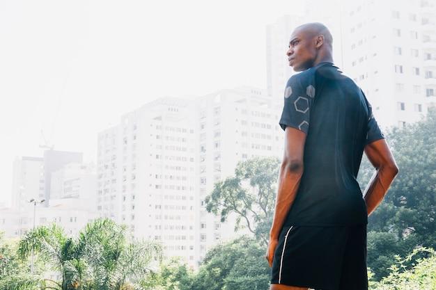 Widok z tyłu fitness młody człowiek stojący przed budynkami