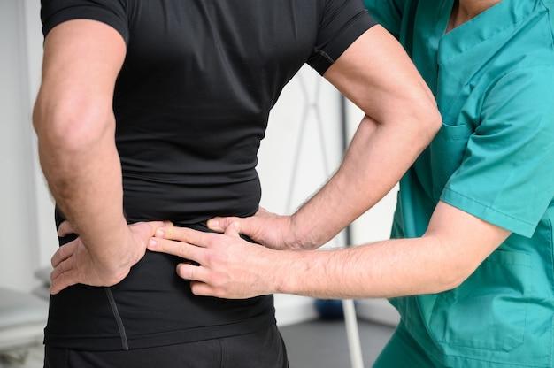 Widok z tyłu fizjoterapeuty bada plecy człowieka.