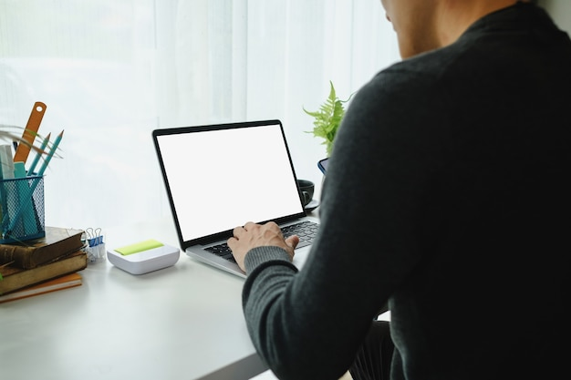 Widok z tyłu freelancer młody człowiek siedzi w swoim wygodnym miejscu pracy i pracy na komputerze przenośnym.