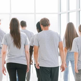Widok z tyłu grupa młodych ludzi przechodząca przez przestronne biuro