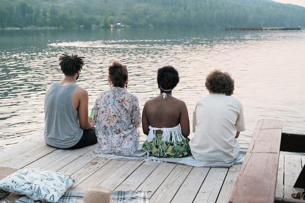 Widok z tyłu grupy przyjaciół odpoczywających na molo i wspólnie cieszących się pięknem przyrody