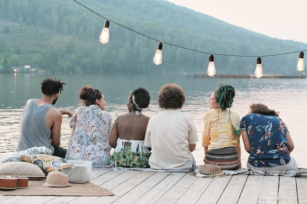 Widok z tyłu grupy przyjaciół siedzących na molo i rozmawiających ze sobą, ciesząc się przyrodą