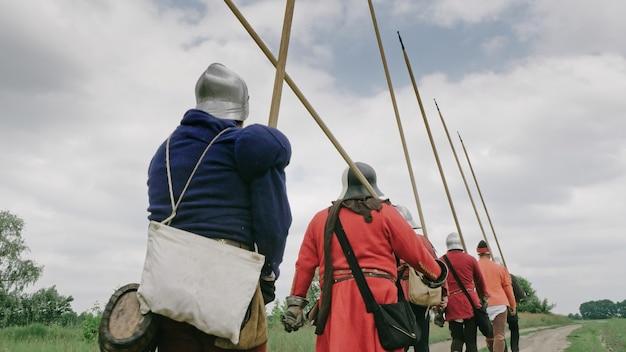Widok z tyłu grupy średniowiecznych rycerzy idących na bitwę.