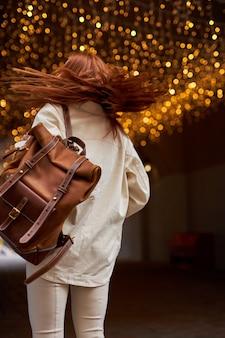 Widok z tyłu hipster kobieta w beżowej kurtce spaceru w ulicy miasta. dobry nastrój nad świecącym świątecznym bokeh. girlandy światła tła miejskiego. portret rudej damy w swobodnym stroju z rozwianymi włosami