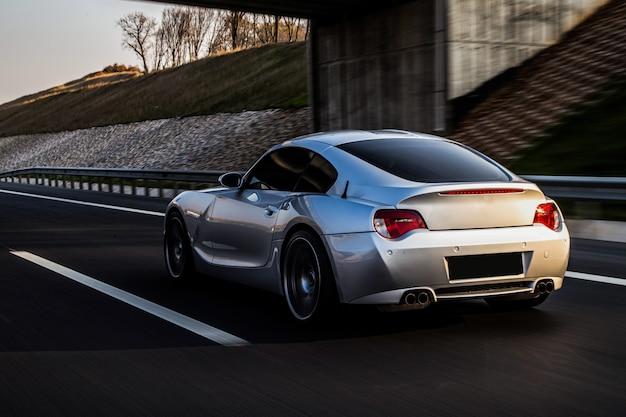 Widok z tyłu i boku metalicznego srebrnego coupe na drodze.