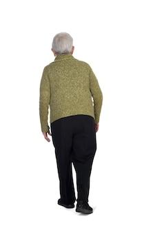 Widok z tyłu i chodzenie starej kobiety na białej ścianie