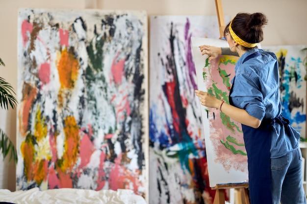 Widok z tyłu inspirowanej utalentowanej kobiety artystki malującej w warsztacie studyjnym w domu