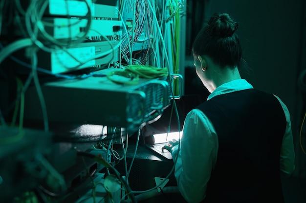 Widok z tyłu inżyniera sieci sprawdzającego serwery podczas pracy z superkomputerem w centrum danych, kopia przestrzeń