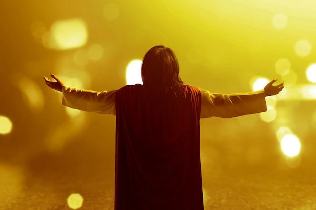 Widok z tyłu jezusa chrystusa podniósł ręce i modlił się do boga