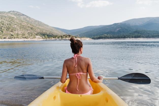 Widok z tyłu kaukaski kobieta w kąpieli nosić trzymając wiosło siedzi na żółtym kajaku w jeziorze w słoneczny dzień. kobieta gotowa do wiosłowania. czas letni. sport, przygoda i przyroda