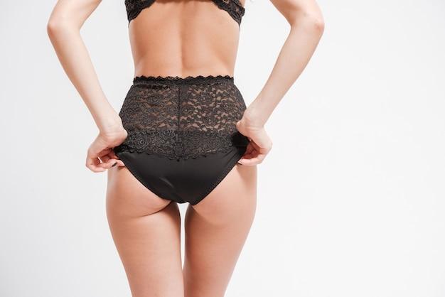 Widok z tyłu kobiecego ciała w seksownej bieliźnie na białym tle