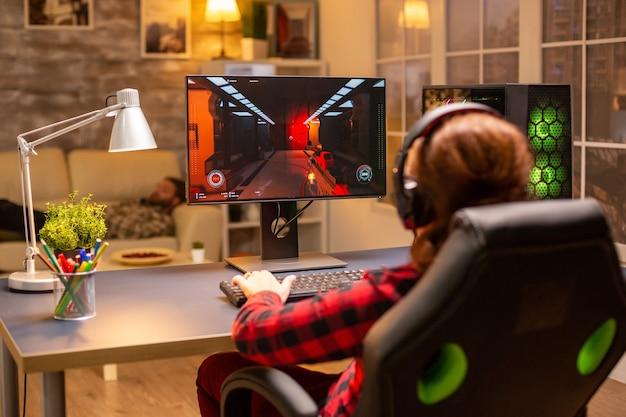 Widok z tyłu kobiecego gracza grającego na potężnym komputerze pc późno w nocy w salonie.