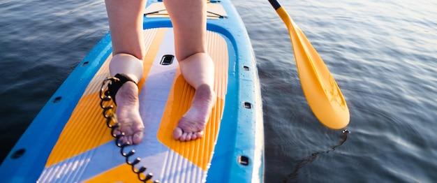 Widok z tyłu kobiecych nóg stojących na żółtym kolorze sup paddleboard