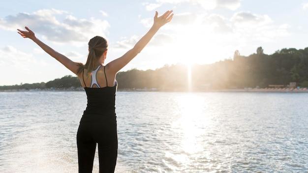 Widok z tyłu kobieta, ciesząc się światłem słonecznym