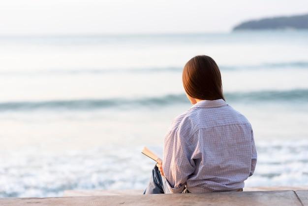 Widok z tyłu kobieta czytająca na plaży