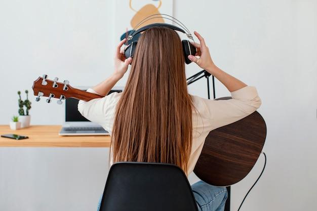 Widok z tyłu kobieta muzyk zakładający słuchawki, aby nagrać piosenkę i grać na gitarze akustycznej