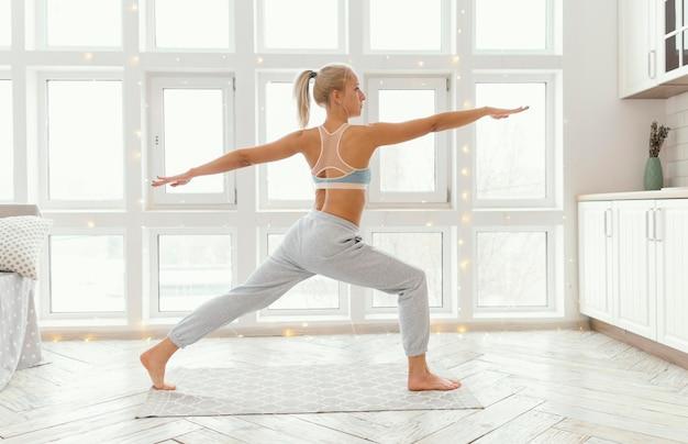 Widok z tyłu kobieta na macie ćwiczeń