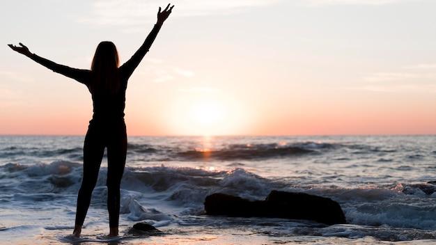 Widok z tyłu kobieta patrząc na zachód słońca z miejsca na kopię