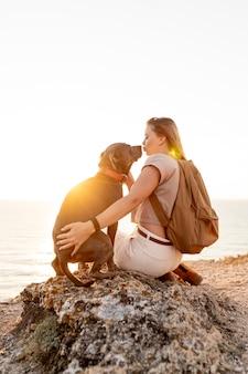 Widok z tyłu kobieta przytulanie psa o zachodzie słońca
