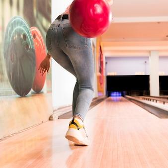 Widok z tyłu kobieta rzuca piłkę do kręgli