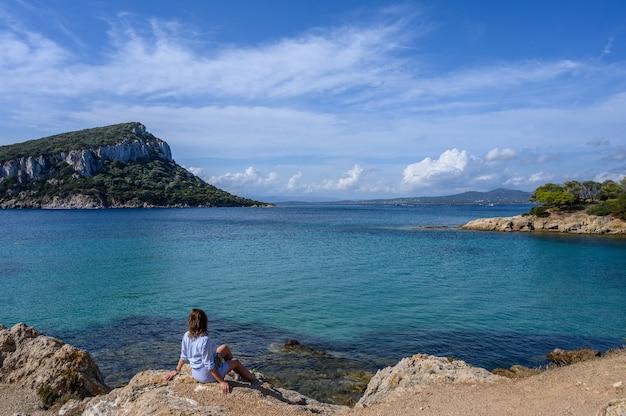 Widok z tyłu kobieta siedząca na skalistym brzegu i patrząca na morze