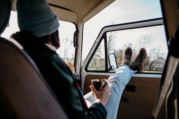 Widok z tyłu kobieta siedząca w furgonetce z wyciągniętymi nogami