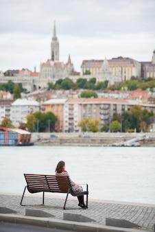 Widok z tyłu kobieta siedzi na ławce na skarpie budapesztu w pobliżu rzeki