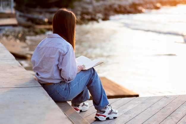 Widok z tyłu kobieta trzyma książkę z miejsca na kopię