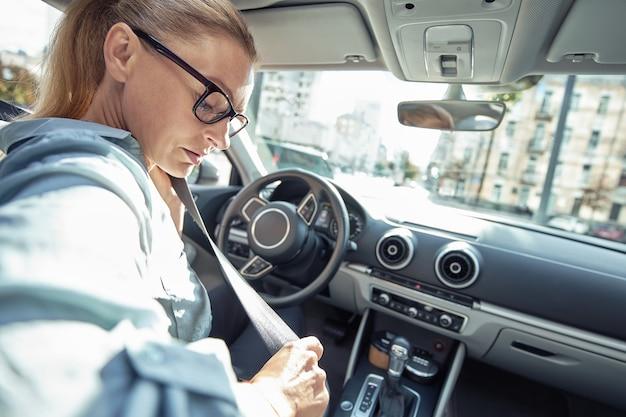 Widok z tyłu kobiety biznesu w średnim wieku siedzącej za kierownicą swojego samochodu i zapinającej siedzenie