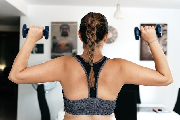 Widok z tyłu kobiety ćwiczenia z hantlami w swoim salonie.