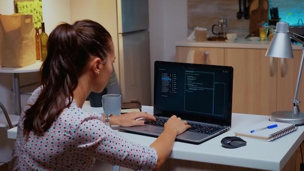 Widok z tyłu kobiety haker kodującej niebezpiecznego wirusa do ataku na bazę danych firmy o północy. programista piszący niebezpieczne złośliwe oprogramowanie do cyberataków przy użyciu urządzenia wydajnościowego późno w nocy.