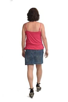 Widok z tyłu kobiety idącej z dżinsową spódnicą na białym tle