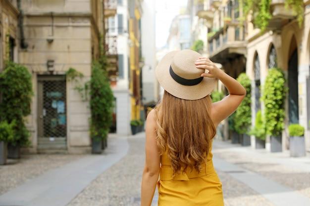 Widok z tyłu kobiety mody podróżnika odwiedzającej dzielnicę brera w mediolanie we włoszech